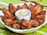 Печени пилешки крилца намазани с масло върху морска сол на фурна